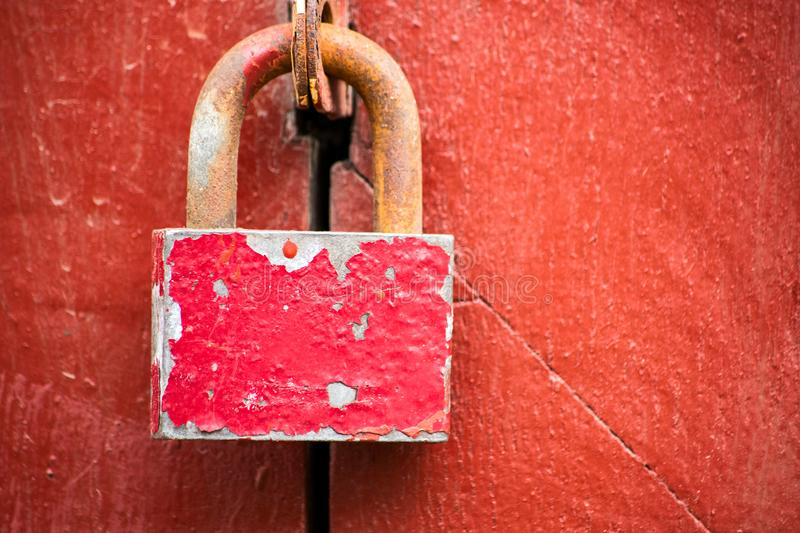 Rusty pink padlock is on the red wall royalty free stock photography