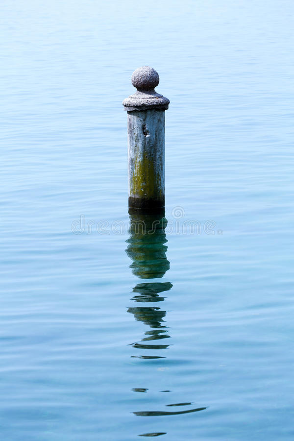 Rusty pole in water stock photo