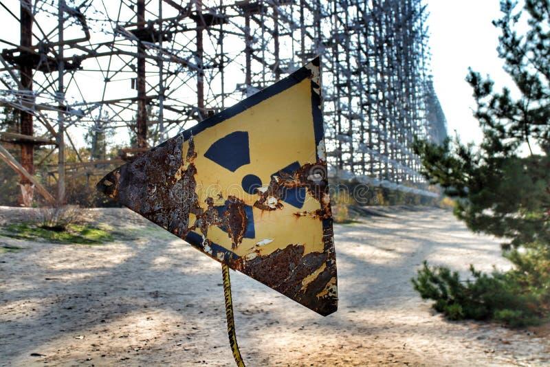 Rusty radioactivity warning sign in the Chernobyl exclusion zone. Rusty radioactivity warning sign in front of the soviet-era Duga-1 radar `Russian Woodpecker` stock image