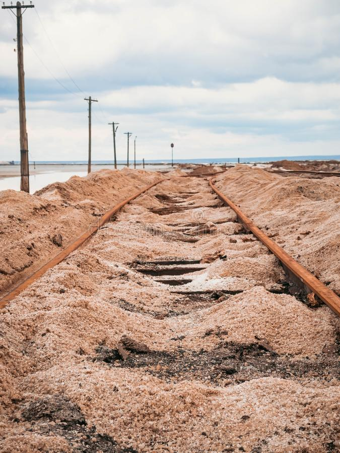 Rusty razy rails and rotten sleepers covered of salt on old railroad tracks on a mound at salt mining lake near brine.  royalty free stock photo