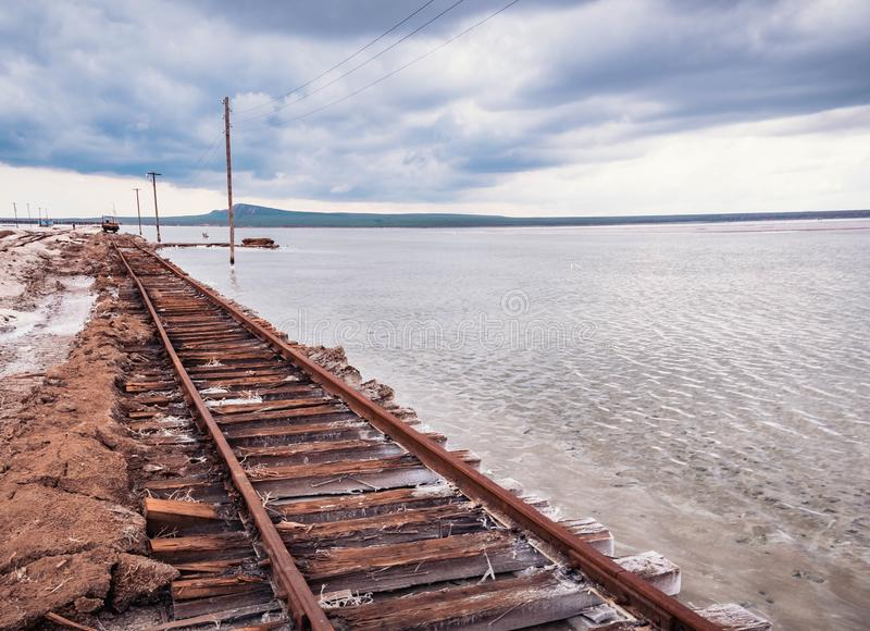Rusty razy rails and rotten sleepers covered of salt on old railroad tracks on a mound at salt mining lake near brine.  royalty free stock image