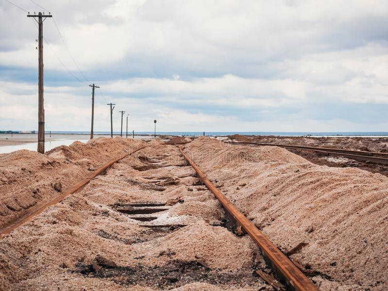 Rusty razy rails and rotten sleepers covered of salt on old railroad tracks on a mound at salt mining lake near brine.  royalty free stock photos
