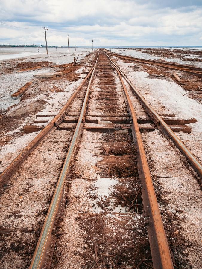Rusty razy rails and rotten sleepers covered of salt on old railroad tracks on a mound at salt mining lake near brine.  stock photos