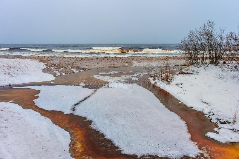 Rusty river under thin ice with waves on the background royalty free stock photography