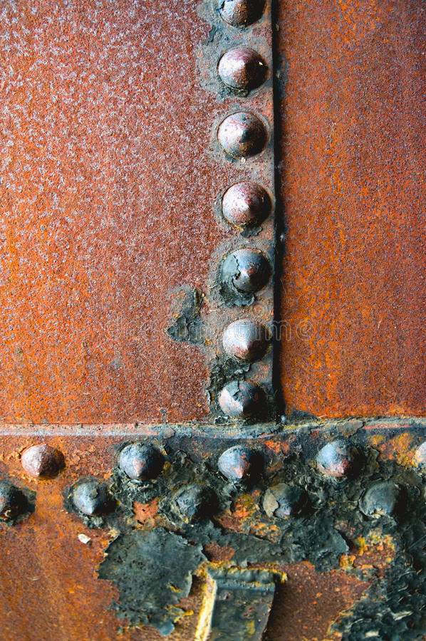 Rusty Rivets Found on Old Metal with a Pitted Texture. A close up of rusted metal with a pitted texture and oxidizing metal rivets stock photos