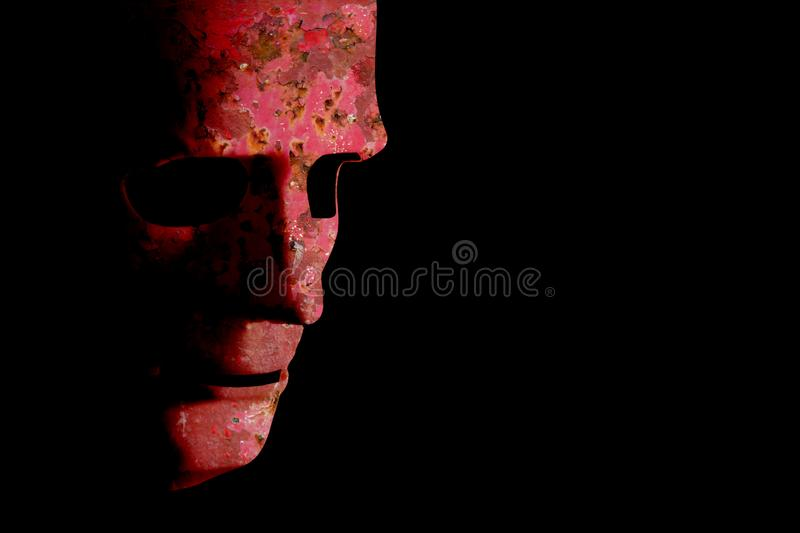 Rusty robotic face old technology. Old robotic decaying face mask. Rusty red grunge texture on a black background with copy space stock photo