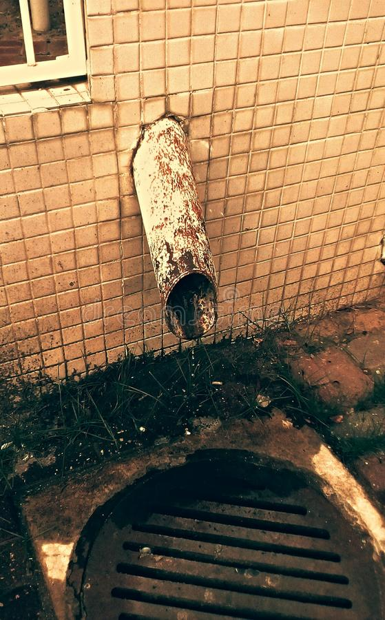 Old place. Rusty rough pipe on old wall in dirty place which is also one iron sewerage royalty free stock photo