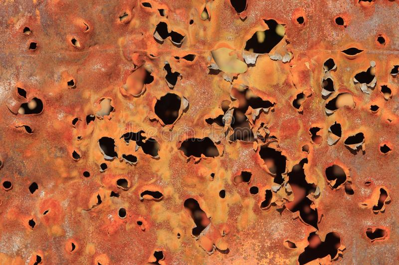 Bullet holes in rusty steel car panel background stock photography