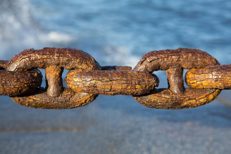 Rusty sea chain close-up. Rusty marine chain close-up on a blue background royalty free stock image