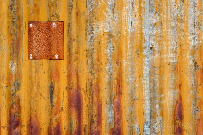 Rusty sheet of corrugated metal wall with metal patches, as an orange textured background royalty free stock images