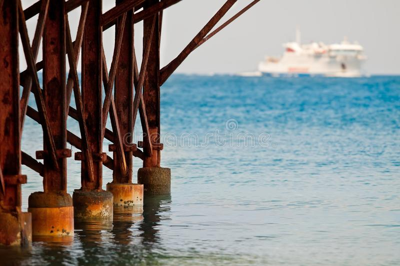 Rusty ship mooring. Look at the rusty pier overlooking the sea with ships stock photos