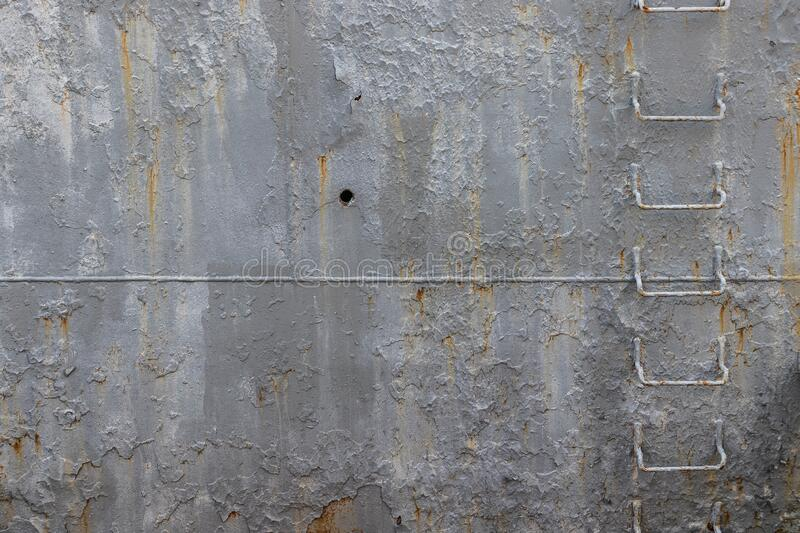 Rusty side of an old warship with an iron staircase. Gray painted metal surface, board of an old warship, background, texture. A ladder of iron staples is welded stock photo