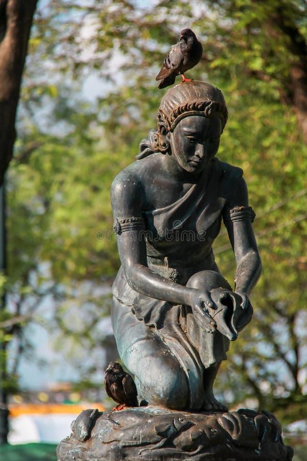 Rusty Statue van Vrouwen die Water gieten door Kroonslak Shell royalty-vrije stock foto's