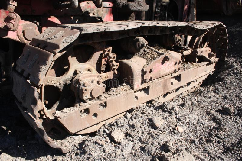 Rusty steel bulldozer track and wheels. An old, rusted, but large steel bulldozer track and wheels, sitting in the mud, waiting for some heavy work royalty free stock images