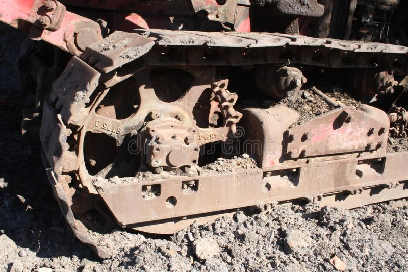 Rusty steel bulldozer track and wheels two. An old, rusted, but large steel bulldozer track and wheels, sitting in the mud, waiting for some heavy work stock image