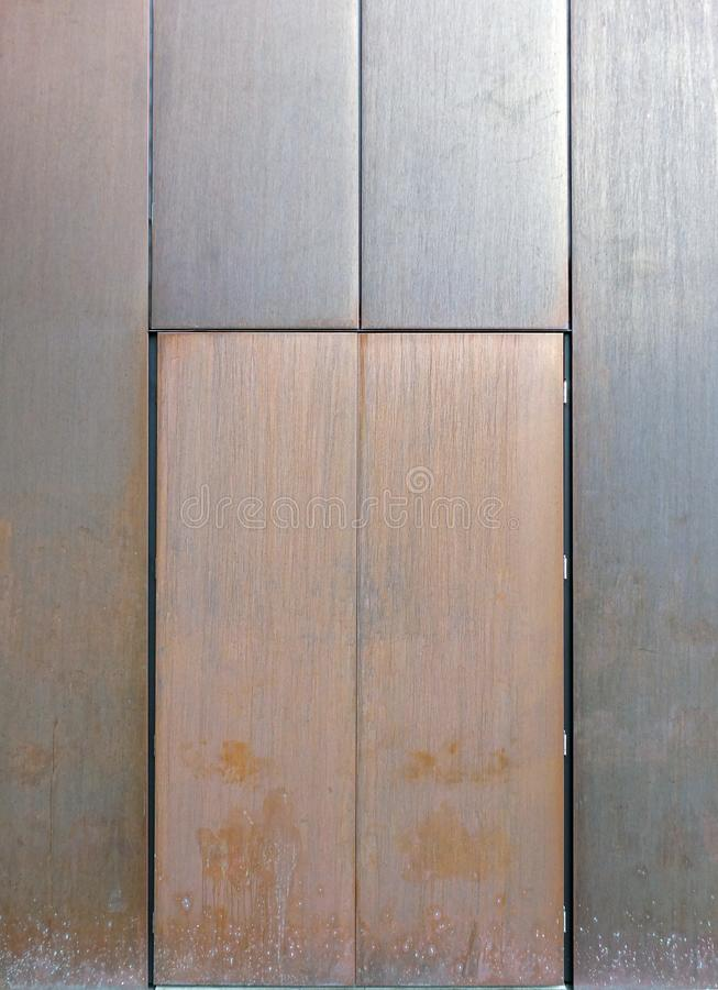 Rusty steel doors in a metal wall with no locks or handles. Rusty stained steel doors in a metal wall with no locks or handles in a metal wall stock image