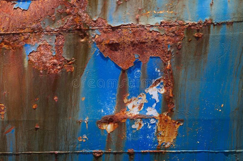 Rusty steel plate. Detail of a heavily corroded ship: blue paint peeling off a steel plate stock image