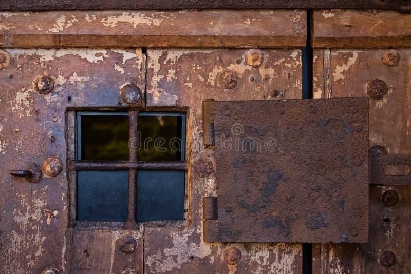 Rusty steel window on very old wooden door on prison stock images
