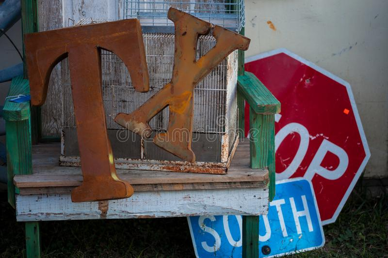 Rusty ``T`` and `X` letters on a wooden chair with stop and south road signs in background stock photos
