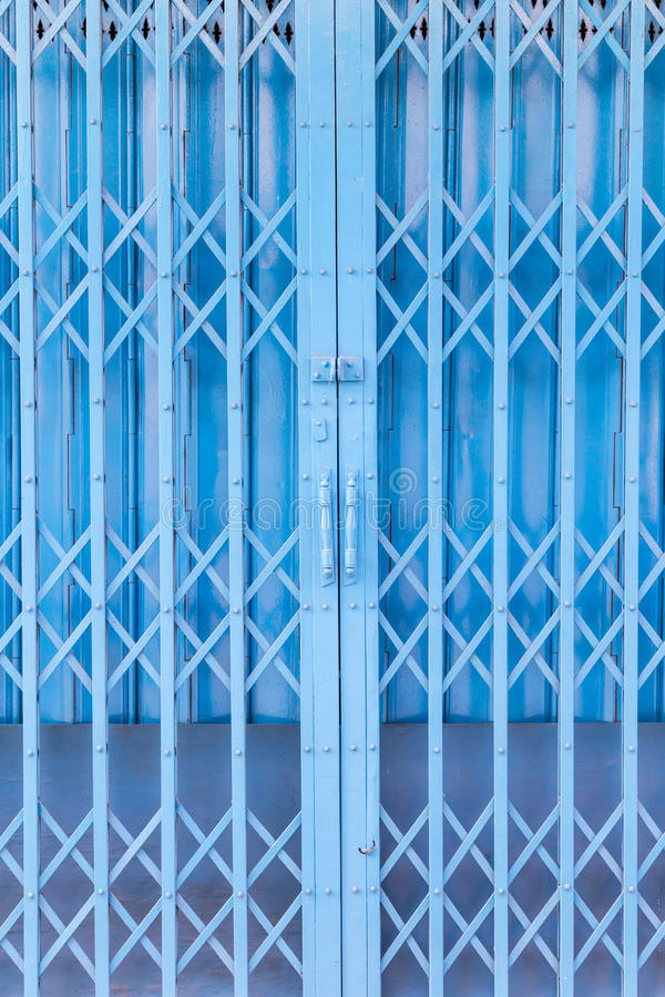 Rusty traditional gate or folding doors. In blue colour stock image