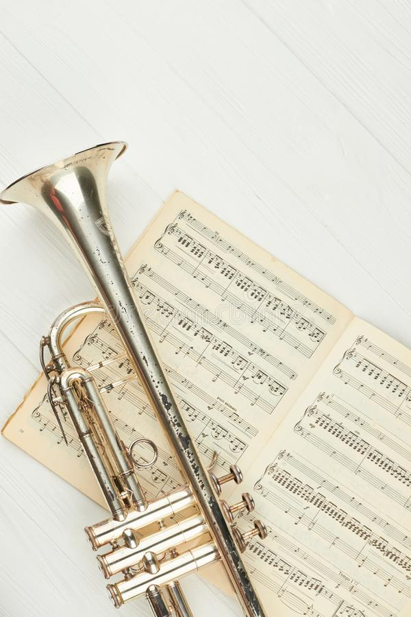 Rusty trumpet on musical notes, top view. royalty free stock images