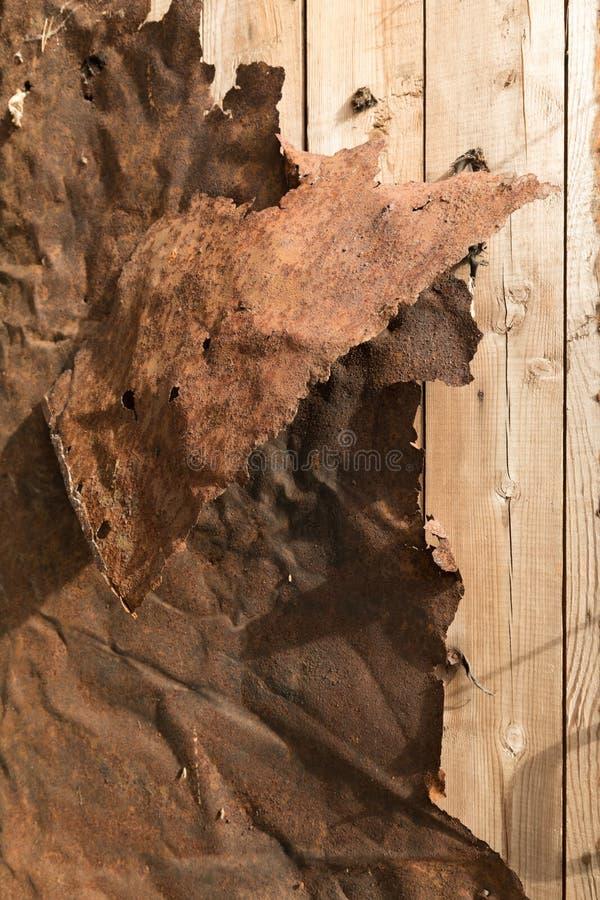 Rusty Twisted Sheet Metal en la pared de madera del tablón foto de archivo