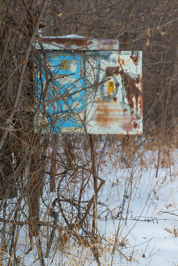 A rusty vintage old phone box I think on a pole that no longer had a phone in it - next to remote area railroad tracks - cold sn stock images