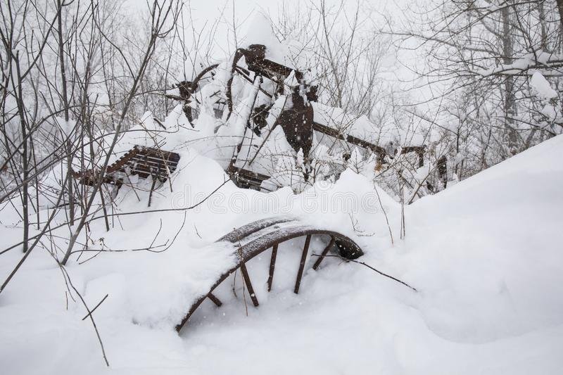A rusty, vintage piece of farm equipment in a snow storm, Ithaca, NY stock photos