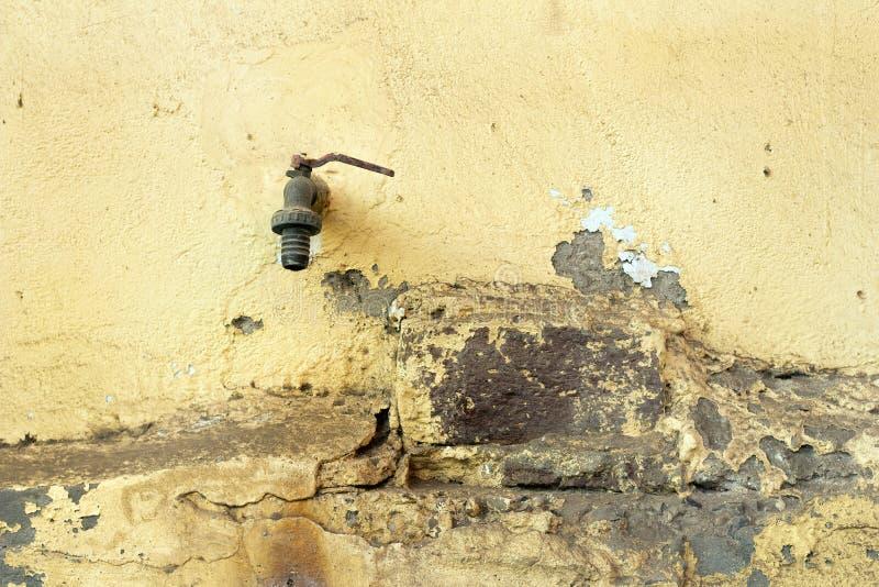 Rusty Water Tap idoso, fundo amarelo da parede, fundo do vintage imagem de stock royalty free