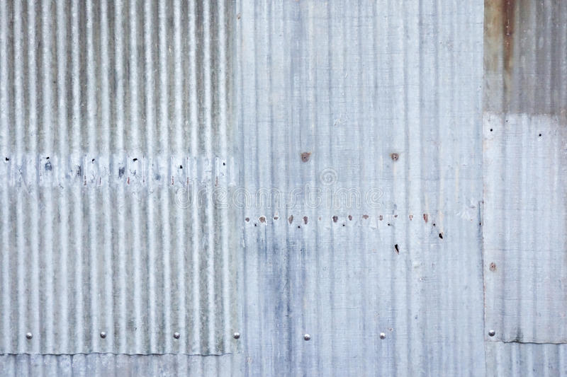 A rusty and weathered looking piece of corrugated metal background and lighting stock photo