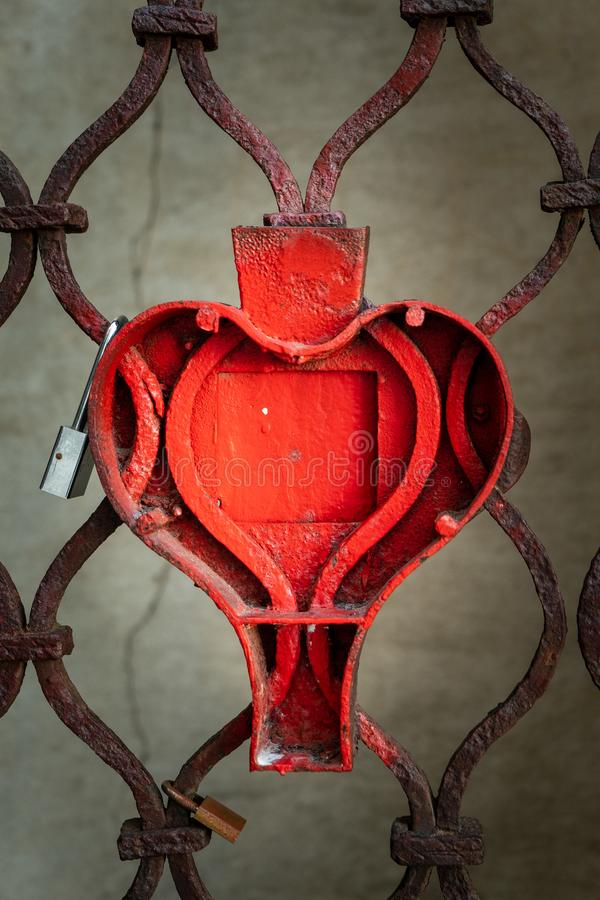 Red metal iron fence with heart shape. Rusty weathered red metal iron fence with heart shapes stock photography
