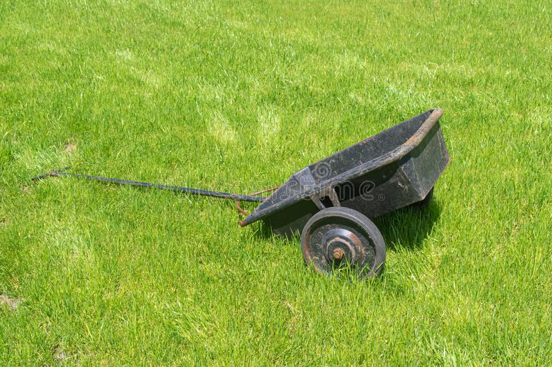 Rusty wheel barrow on a summer lawn stock photo
