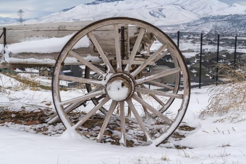 Rusty wheel of a wooden cart against a rocky ground covered with snow in winter. Homes, snow capped mountain, and cloudy sky can be seen in the frosty stock photography