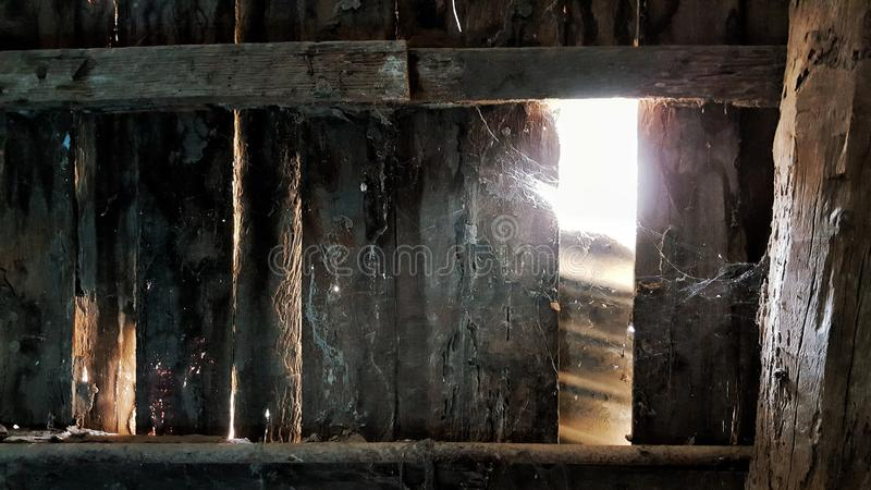 The rusty wooden wall with the sunshine through the weathered holes. stock photos