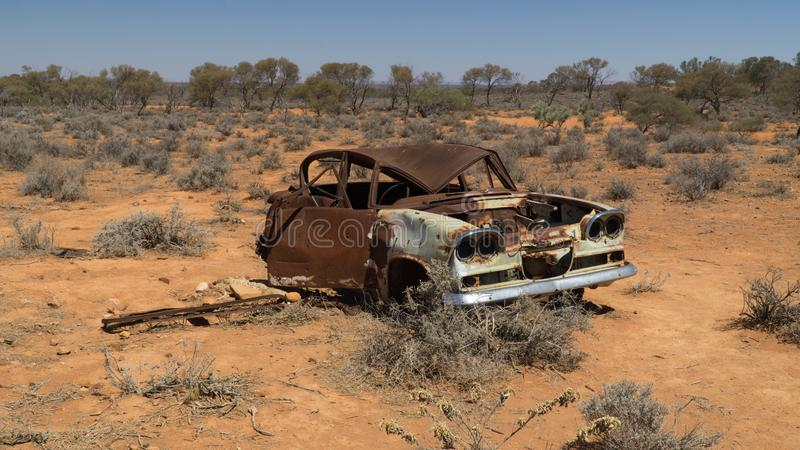 Rusty wreck of crashed car in the middle of desert warning to inattentive drivers, Stuart Highway, Australia royalty free stock image