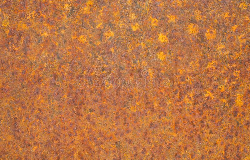 Rusty yellow metal surface. Saturated orange, red, grunge rusty metal texture background. Corroded metal plate wallpaper. Typical corrosion on damaged metal royalty free stock photography