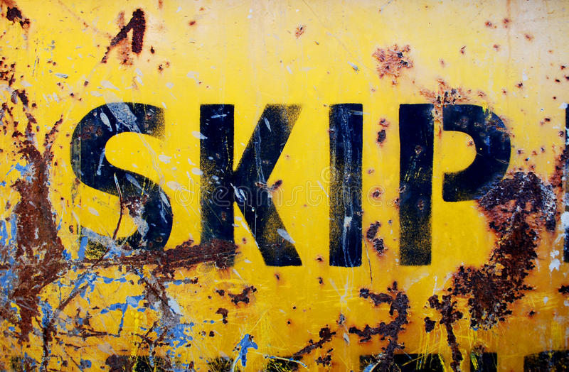 Rusty yellow skip. The side of a rusty industrial skip or dumpster with peeling yellow paint royalty free stock photos
