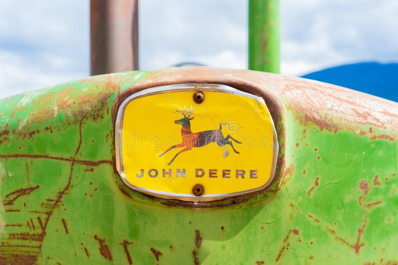 Rusy, old antique John Deere tractor, front nose with the full logo, showing the deer and word mark. Green and yellow classic stock photo