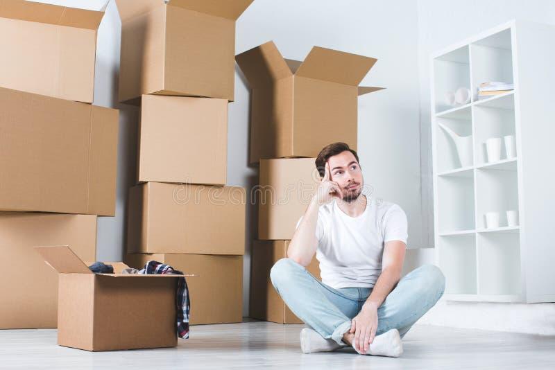 Ruszać się w domu Mężczyzna marzy obsiadanie na podłoga w tła pudełku zdjęcia stock