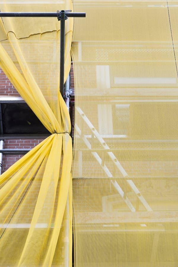 Rusztować z żółtymi siatkami zabezpieczająca podczas odświeżania zdjęcie stock