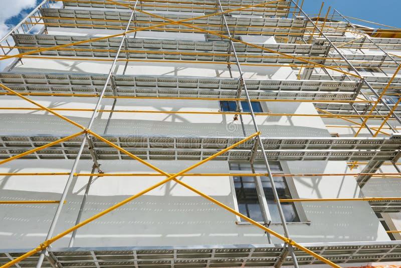 Rusztujący blisko nowego domu, buduje powierzchowność, przemysł, biel ściana i okno, budowy i naprawy, koloru żółtego drymba obraz royalty free