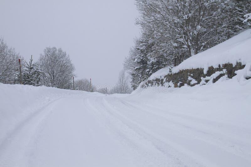 Ruta montañosa cubierta de nieve en invierno foto de archivo