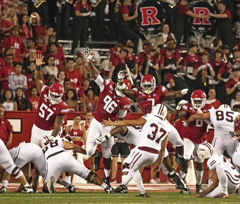 Rutgers Celebrates 150 Years of Intercollegiate Football. Huge Rutgers linemen try in vain to block the extra point kick from Massachusetts.  Rutgers fell behind royalty free stock photo