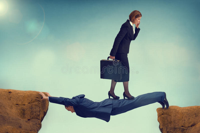 Ruthless business woman walking over a vulnerable businessman stock image