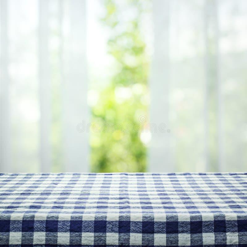 Rutig bordduktexturöverkant på suddighet av gardinen med fönstersiktsgräsplan från trädträdgårdbakgrund royaltyfri bild