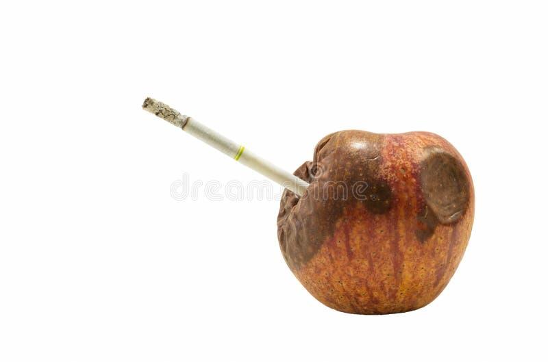 Ruttet äpple med cigaretten royaltyfri foto