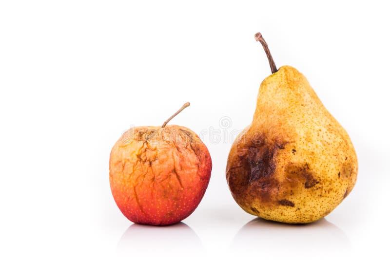 Ruttet och förmultna det röda äpplet och päronet på vit bakgrund fotografering för bildbyråer
