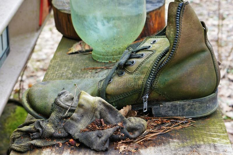 Ruttet piska mäns skor som täckas med den gröna formen royaltyfria bilder