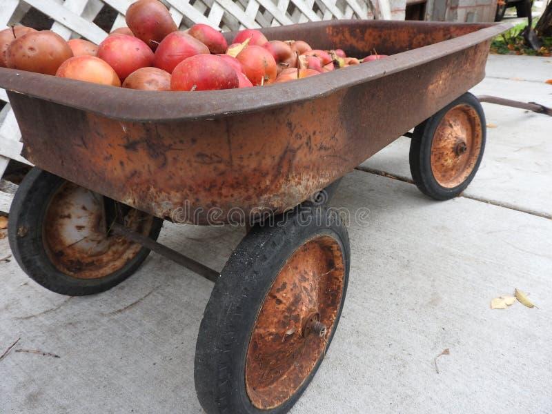Ruttna äpplen och en vagn arkivbilder