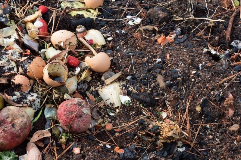 Ruttna kök skrota kompost på jord som är blandad med, sörjer visare och bränt trä arkivbilder